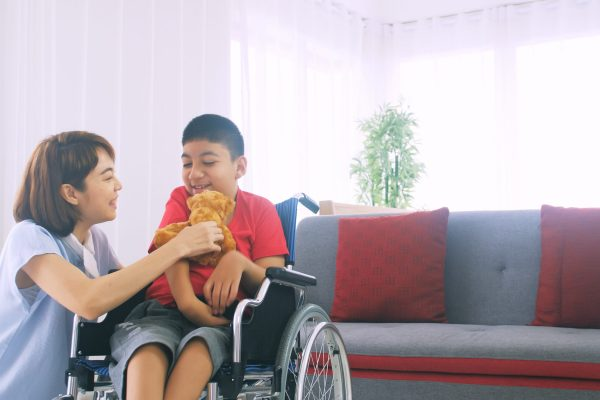 Happy family with mother and disabled son spending time together at home.